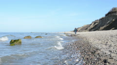 People walking along at the Baltic Sea looking for fossils. Stock Footage