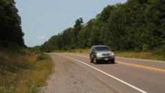 Silver SUV passing on Highway 118 in Haliburton County, Ontario, Canada. - stock footage