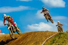Motocross riders on the race Stock Photos