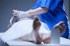 nurse lying the body of corpse - stock photo