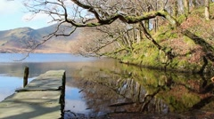 Tree Reflections over beautiful water with stone pier Lake District Countryside Stock Footage