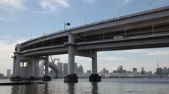 Rainbow Bridge and Tokyo cityscape from Daiba Park, Tokyo, Japan Stock Footage