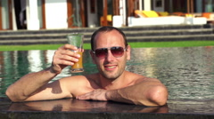Man raising toast with drink in pool, super slow motion, 240fps HD Stock Footage