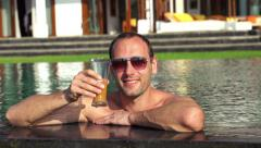 Happy man raising toast with drink in pool HD Stock Footage