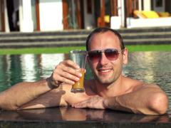Happy man raising toast with drink in pool NTSC Stock Footage