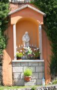 Votive capitals with the statue of the madonna in the village Stock Photos