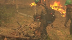 Firefighters with chain saw cutting log being chased by fire - stock footage