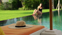 Hat on sunbed, sexy woman in background by pool, super slow motion HD - stock footage