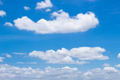 fluffy white clouds and bright blue sky. - stock photo