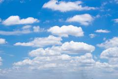 Fluffy white clouds and bright blue sky. Stock Photos