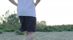 Man jogging barefooted through the sand Stock Footage