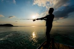 Siluette of unidentified man fishing with rod Stock Photos