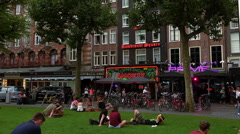 People relaxing on a meadow in front of a coffeeshop - stock footage