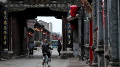 People riding bike through city gate in Pingyao ancient county Stock Footage