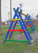 Colorful child playground with swing on rural field Stock Photos