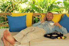 Handsome man talking on cellphone and relaxing on gazebo bed in garden NTSC Stock Footage