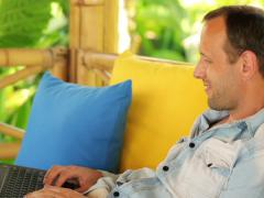 young man working with laptop on gazebo bed in garden NTSC - stock footage