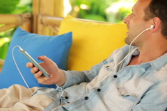young man listening to the music on gazebo bed in garden NTSC - stock footage