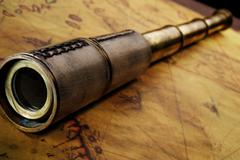 Close-up of a spyglass on the old map Stock Photos