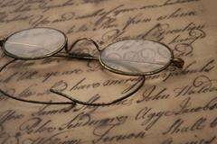 Old glasses on the vintage document Stock Photos