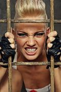 Punk girl behind bars Stock Photos