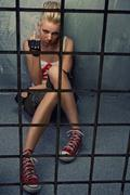 Punk girl showing middle finger behind bars Stock Photos