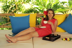 Pretty woman relaxing with coffee on gazebo bed in garden NTSC Stock Footage