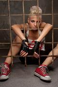 Punk girl behind bars. Stock Photos