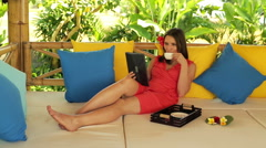Pretty woman relaxing with tablet and coffee on gazebo bed in garden HD Stock Footage