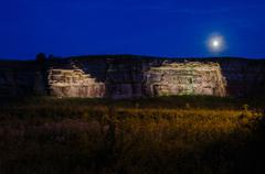 Moonlight over illuminated cliffs Stock Photos