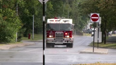 Firetruck driving fast with lights and sirens near camera Stock Footage