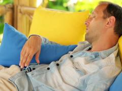 Young handsome man sleeping on comfortable gazebo bed in garden NTSC Stock Footage