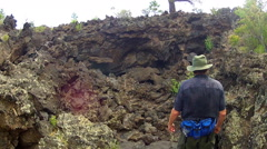 Man Looks At Lichen Covered Lava- Sunset Crater National Monument Stock Footage
