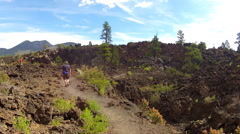 Men Hike Lava Field Trail- Sunset Crater National Monument Stock Footage