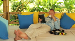 Man drinking coffee and reading news on tablet computer in garden HD Stock Footage