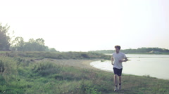 Man running back and forth next to the river Stock Footage