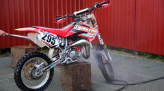 A dirt bike getting cleaned with a water hose Stock Footage