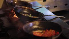 Food sizzling in pans over open flame stove kitchen chef Stock Footage