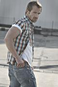 Rebellious man wearing jeans and a plaid shirt at a gas station, turning roun Stock Photos