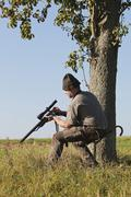 Hunter on a driven hunt, reloading his rifle Stock Photos