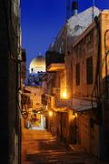 Evening mood with a deserted alleyway in the arab quarter, with the dome of t Stock Photos
