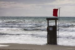 lifeguard watch tower on the beach of playa torá with a red flag and waves,  - stock photo