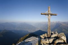 summit cross on mt ifinger or ivigna in morning light, meran or merano below, - stock photo