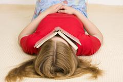 Girl, 17 years, lying on the floor covering her face with a book Stock Photos