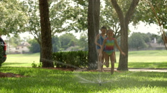 two little girls jump over sprinkler and run towards camera - stock footage