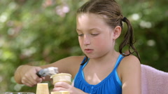 little girl spooning ice cream on a cone - stock footage