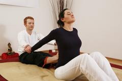 Qigong coach doing relaxation exercises with a young woman, chinese gymnastic Stock Photos