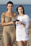 Two young women drinking wine on a beach Stock Photos