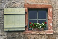 window with shutters and geraniums, eberbach, hesse, germany, europe - stock photo