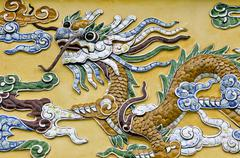 Dragon figure made of porcelain fragments on a yellow wall, hoang thanh imper Stock Photos